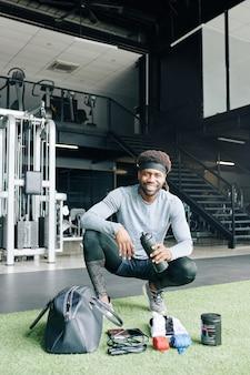 Entraîneur de fitness gai dans la salle de gym