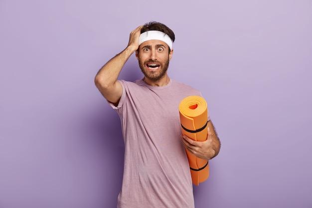Un entraîneur de fitness perplexe touche la tête, tient un karemat enroulé, s'entraîne dans une salle de sport
