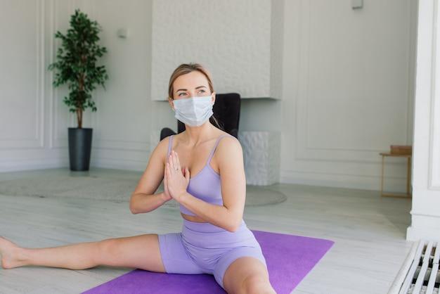 Un entraîneur de fitness sportif féminin séduisant portant un masque médical blanc fait des exercices sur un tapis de yoga à la maison.