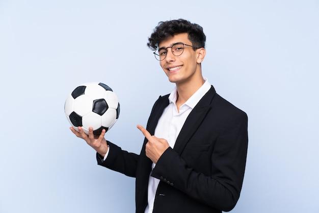 Entraîneur de football argentin sur mur bleu isolé et en le pointant