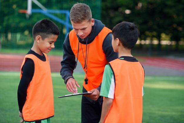 L'entraîneur de football instruit les joueurs de football adolescents. le jeune entraîneur professionnel explique aux enfants la stratégie du jeu.