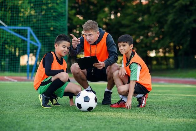 L'entraîneur de football montre une stratégie de jeu de football à ses joueurs à l'entraînement.