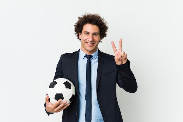 Entraîneur de football tenant un ballon montrant le signe de la victoire et souriant largement.