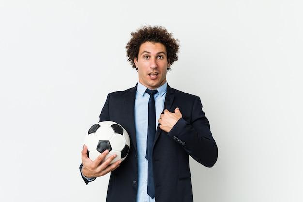 Entraîneur de football tenant un ballon surpris pointant vers lui-même, souriant largement.