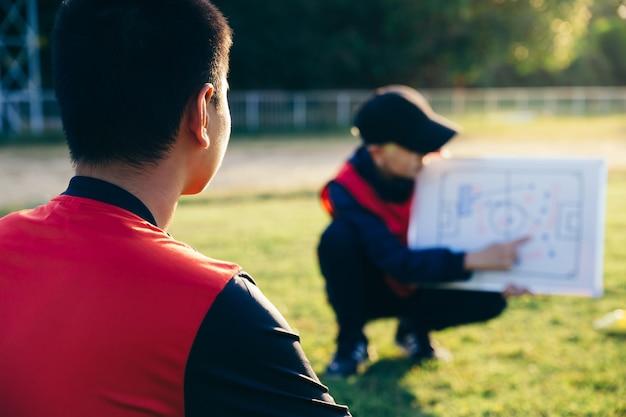 Entraîneur formant une tactique pour le joueur de football adolescent asiatique.