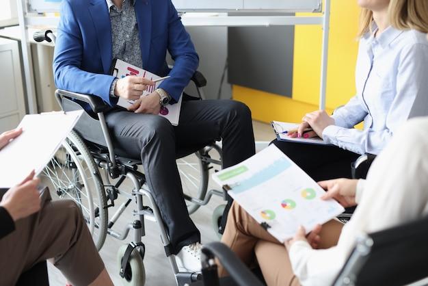 Entraîneur handicapé en fauteuil roulant assis avec un groupe d'auditeurs et tenant des documents avec des graphiques en hi...