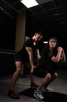 L'entraîneur de l'homme entraîne une fille dans un costume ems dans la salle de sport