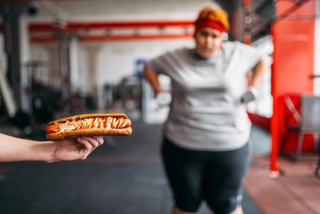 Un entraîneur avec un hot-dog oblige une grosse femme à faire de l'exercice