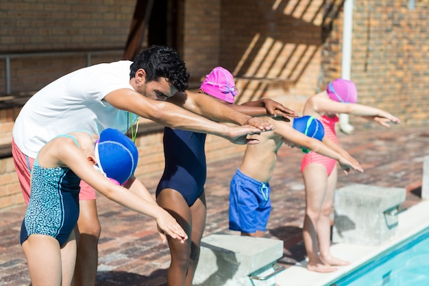 Entraîneur masculin aidant les petits nageurs à sauter dans la piscine