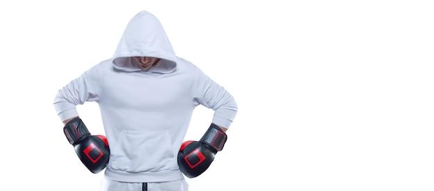 Entraîneur masculin posant dans le studio avec des gants de boxe. sweat à capuche blanc. concept d'arts martiaux mixtes.