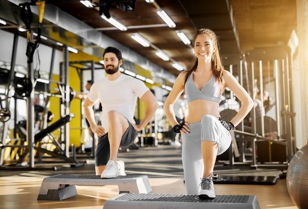 Entraîneur musculaire fort attrayant montrant l'exercice des jambes avec stepper à une jolie fille souriante avec des gants dans la salle de gym.