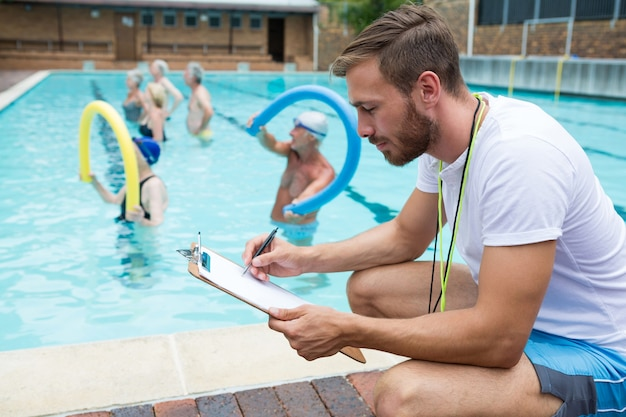 Entraîneur de natation écrit sur le presse-papiers près de la piscine