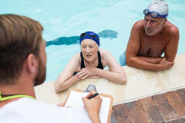 Entraîneur de natation interagissant avec un couple de personnes âgées au bord de la piscine