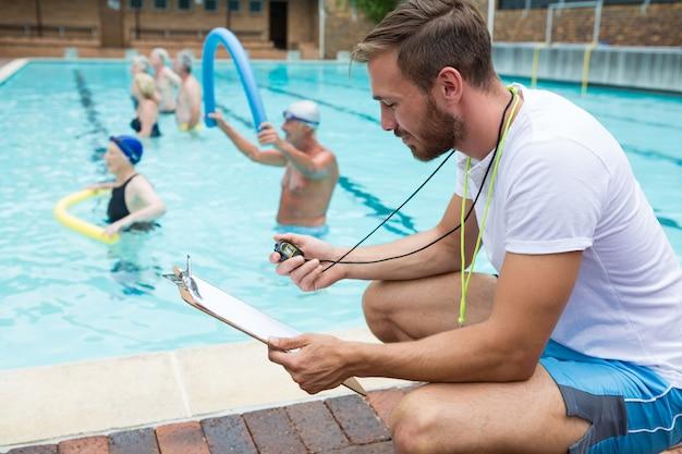 Entraîneur de natation souriant regardant le presse-papiers près de la piscine au centre de loisirs
