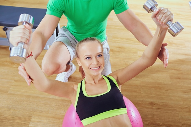Entraîneur personnel aide une fille sportive à faire des exercices avec haltère