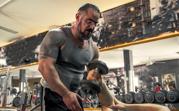 Entraîneur personnel bodybuilder dans un entraînement de gym