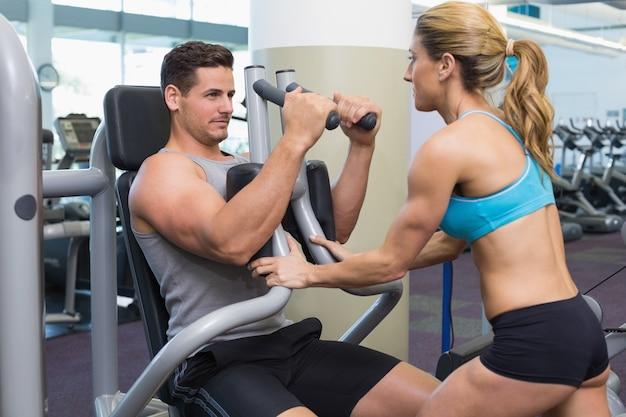 Entraineur personnel coaching bodybuilder en utilisant une machine de musculation