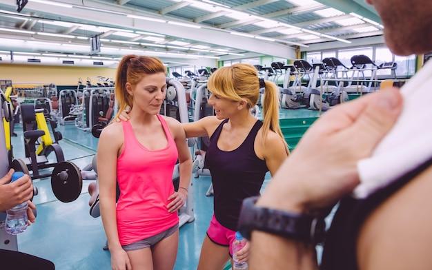 Entraîneur personnel encourageant à triste jeune femme après une dure journée d'entraînement dans la salle de sport