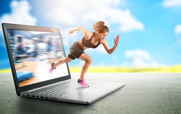 Un entraîneur personnel fait une leçon de yoga à la gym via internet et un ordinateur portable