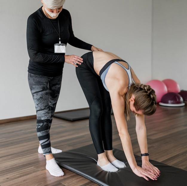 Entraîneur personnel féminin et client dans une salle de sport