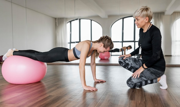Entraîneur personnel féminin et client utilisant un ballon de fitness