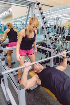Entraîneur personnel femme criant à l'homme musculaire dans un entraînement de développé couché avec haltères au centre de remise en forme motivation dans le concept de formation.
