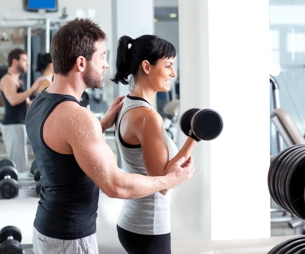 Entraîneur personnel femme gym avec musculation