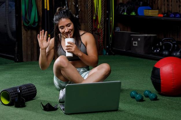 Entraîneur personnel saluant devant l'ordinateur après avoir donné un cours en ligne en prenant un verre