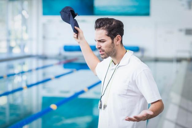 Un entraîneur sérieux en colère contre quelqu'un à la piscine