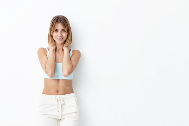 Entraîneur de sport féminin au corps mince, vêtu de vêtements de sport, gardant les mains sur le cou, ayant une expression heureuse en attendant ses élèves. femme athlétique va courir, isolé sur un mur blanc