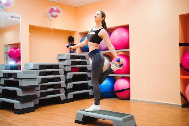 Entraîneur sportif faisant des cours d'aérobic avec des steppers. sport