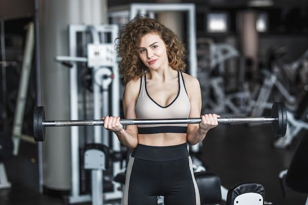 Entraîneur sportif jeune fille blonde en vêtements de sport avec des haltères dans une salle de sport, s'exerçant avec une barre