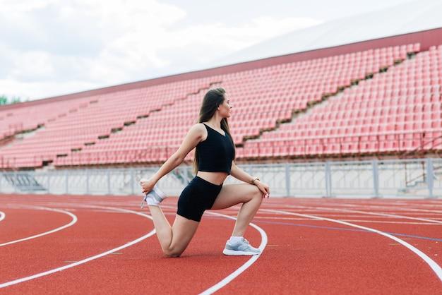 Une entraîneure aux cheveux noirs se tient sur la piste de course rouge du stade, vêtue d'un uniforme de sport.