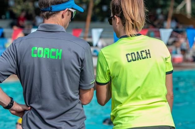 Des entraîneurs de natation masculins et féminins travaillant ensemble dans une piscine extérieure