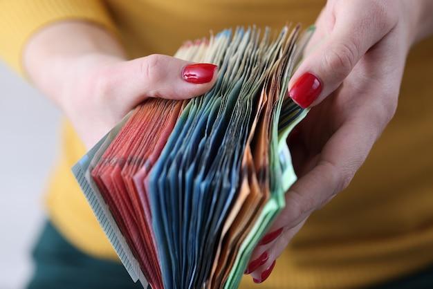 Entre les mains des femmes, des billets en euros de différentes dénominations. petites et moyennes entreprises