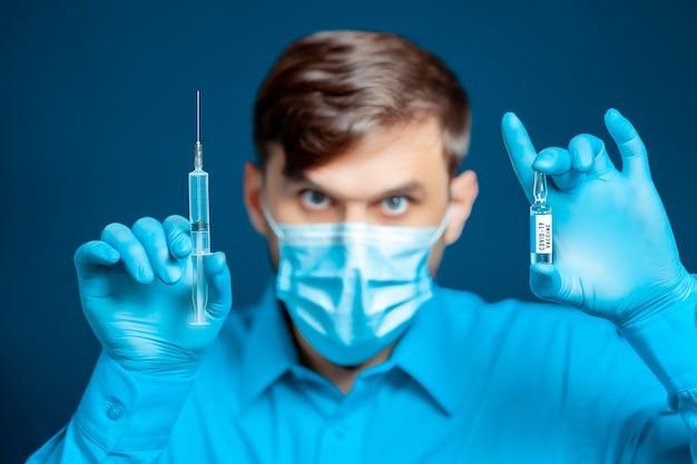 Entre les mains d'un médecin, d'un médecin portant un masque médical et des gants, vêtu d'un uniforme bleu, d'une seringue d'injection et d'un vaccin contre le coronavirus