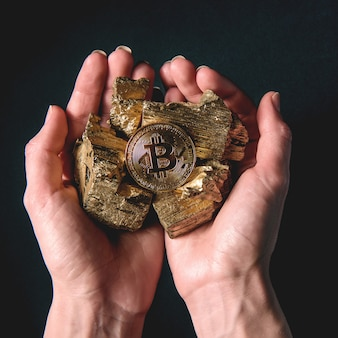 Entre les mains de pièces d'or et de bitcoins. concept d'exploitation minière rentable