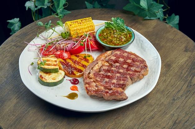 Entrecôte de boeuf avec légumes grillés et sauce verte dans une assiette blanche