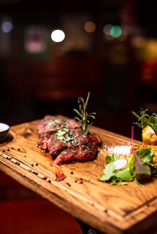 Entrecôte de boeuf viande de steak grillée avec flammes de feu sur planche à découper en bois avec branche de romarin, poivre et sel. chef cuisinier délicieux barbecue grill.