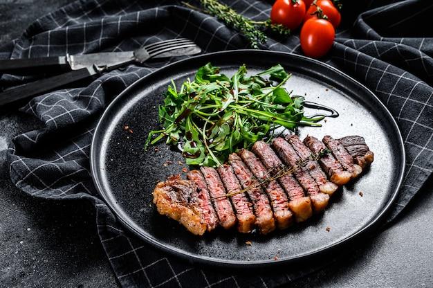 Entrecôte grillée cuite, viande de bœuf marbrée à la roquette. surface noire. vue de dessus