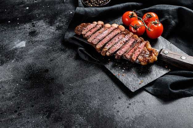 Entrecôte grillée en tranches sur un couperet à viande. fond noir. vue de dessus. espace copie