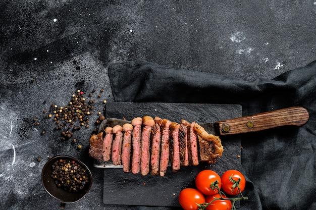 Entrecôte grillée en tranches sur un couperet à viande. surface noire. vue de dessus. espace copie