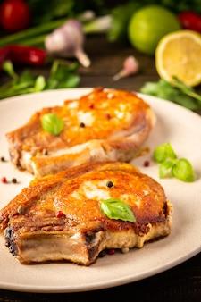 Entrecôte de porc frit sur l'os, morceaux cuits de viande de porc avec des feuilles de basilic et des épices, steak sur l'os dans une assiette sur fond de bois
