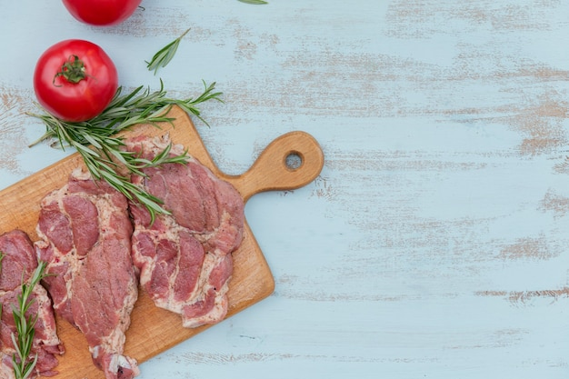 Entrecôte de steak de viande fraîche crue, tomates, romarin et assaisonnements sur planche à découper en bois