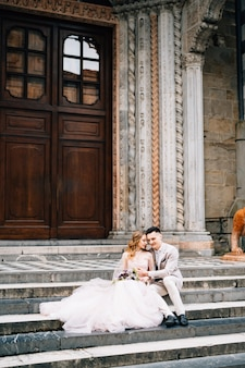 Entrée de la basilique de santa maria maggiore à rome les jeunes mariés sont assis sur les marches étreignant