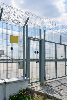 Entrée de la clôture par le gril et le fil de fer barbelé. espace pour le texte sur une plaque.