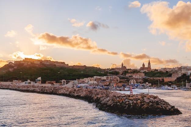 Entrée dans la baie, front de mer avec phare en bord de mer au coucher du soleil.