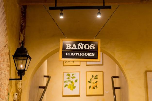Entrée des salles de bains avec panneaux en espagnol et en anglais.