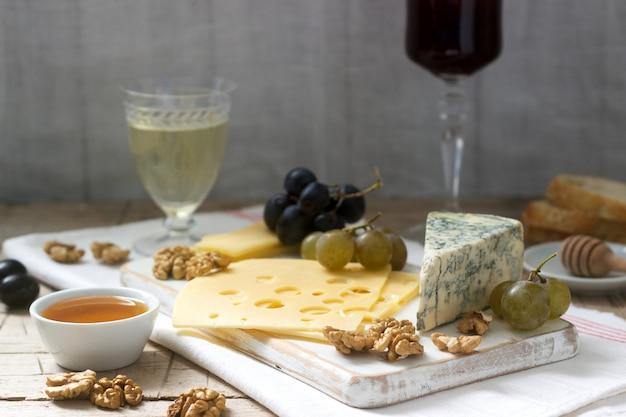 Entrées de différents types de fromage, raisins, noix et miel, accompagnées de vin blanc et rouge