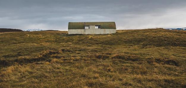 Entrepôt abandonné dans une terre en friche près d'un pré.